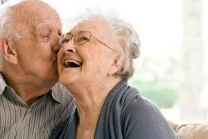 elderly husband kissing his wife on the cheek
