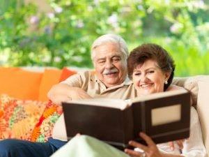 senior couple smiling as they look through a photo album