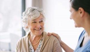 senior female smiling at her caregiver